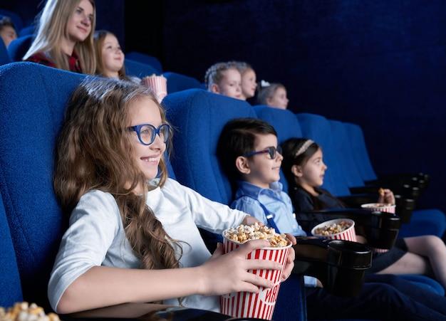 Garota feliz de óculos comendo pipoca e rindo no cinema