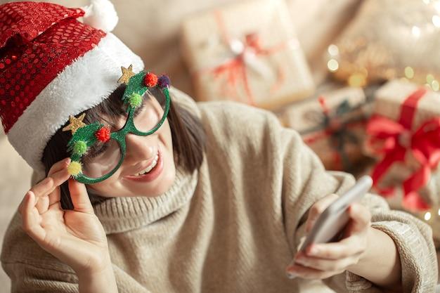 Garota feliz de óculos engraçados de natal e chapéu de papai noel com um telefone nas mãos.