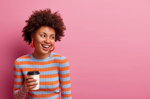 Garota feliz de pele escura com cabelo afro, vestida com um macacão listrado, aproveita a pausa para o café, segura um copo de papel de cappuccino, sorri amplamente, posa