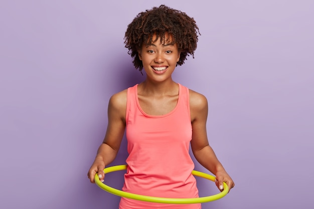 Garota feliz de pele escura gira o bambolê, gosta de exercícios ativos e treinamento de ginástica e usa equipamentos de ginástica