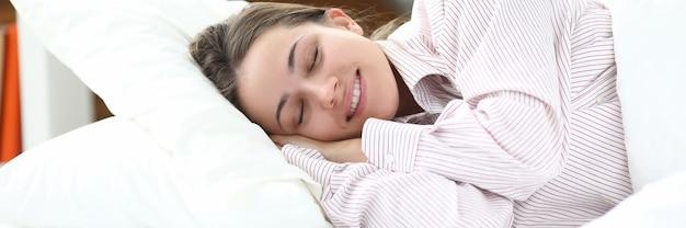 Garota feliz de pijama deitada na cama fechando os olhos