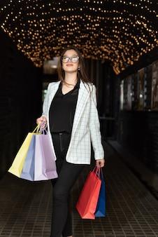 Garota feliz depois de fazer compras com sacos de papel multicoloridos. cidade à noite. quadro vertical.