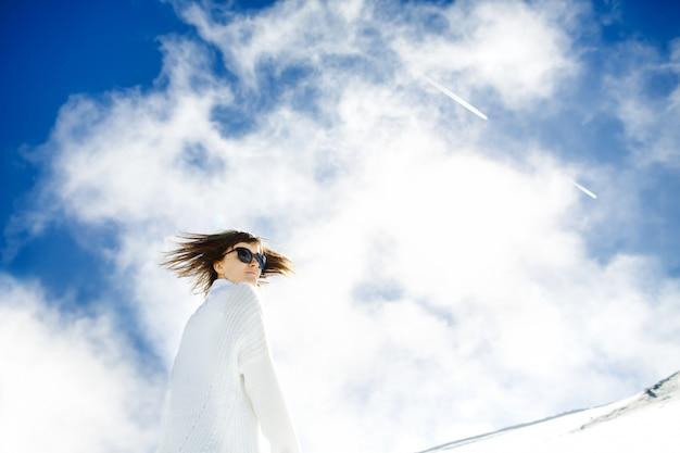 Garota feliz, descansando na neve e no sol