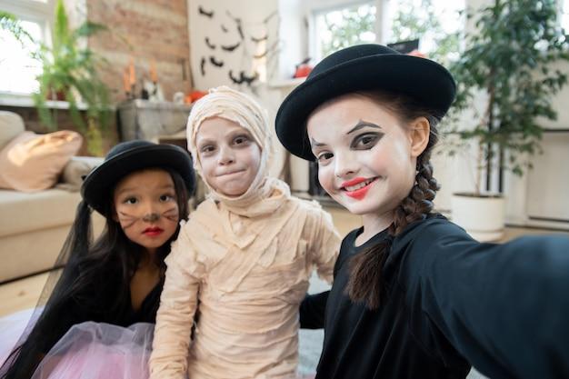 Garota feliz do dia das bruxas fazendo selfie com duas crianças fantasiadas