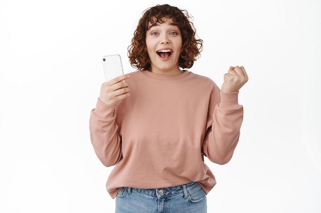 Garota feliz e bem-sucedida vencendo no celular, atingir a meta no aplicativo, celebrar a vitória ou vitória no smartphone, ficar maravilhada no branco