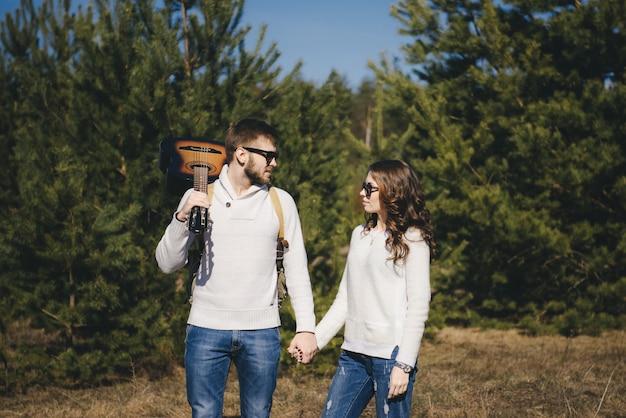 Garota feliz e cara com mochila de turista e guitarra andando na natureza, conceito de história de amor de viagem, foco seletivo