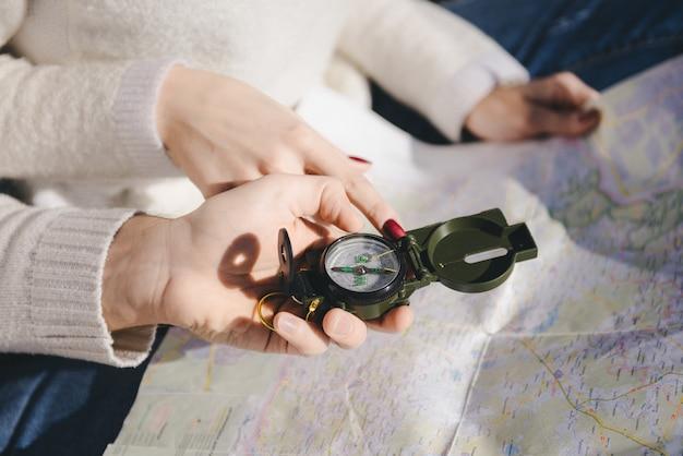 Garota feliz e cara com uma mochila de turista e uma guitarra olhando para a rota com uma bússola e um mapa, conceito de história de amor de viagem, foco seletivo