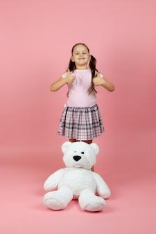 Garota feliz e despreocupada fazendo sinal de positivo com um ursinho de pelúcia branco perto de seus pés