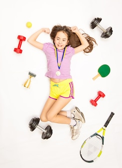 Garota feliz e esportiva posando com medalha de ouro e equipamentos esportivos