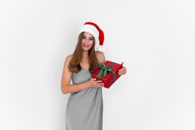 Garota feliz e positiva com chapéu de papai noel segurando um presente de natal enquanto fica na festa de fundo branco