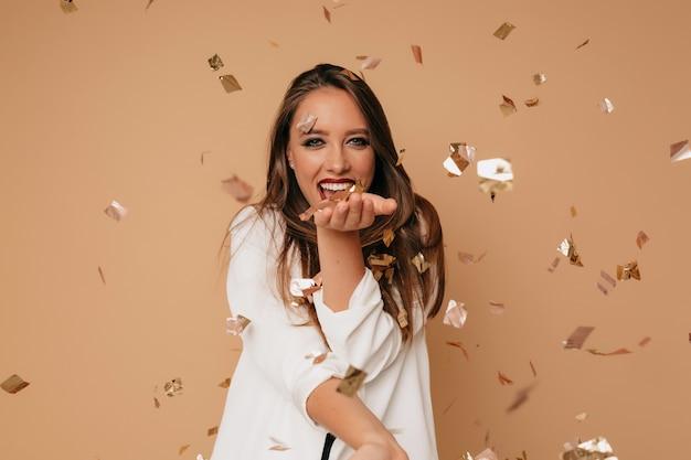 Garota feliz e saída com uma jaqueta branca soprando confetes durante a sessão de fotos sobre fundo bege