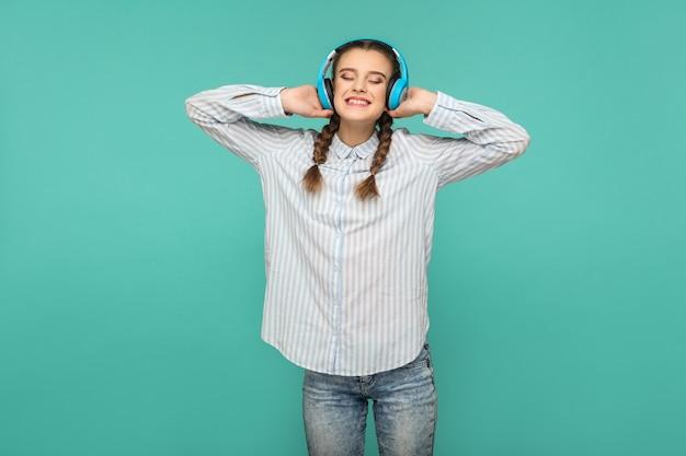 Garota feliz e satisfeita com camisa azul listrada e penteado pigtail, ouvindo música favorita em pé com fones de ouvido, olhos fechados e sorriso cheio de dentes, tiro em estúdio interno, isolado no fundo verde