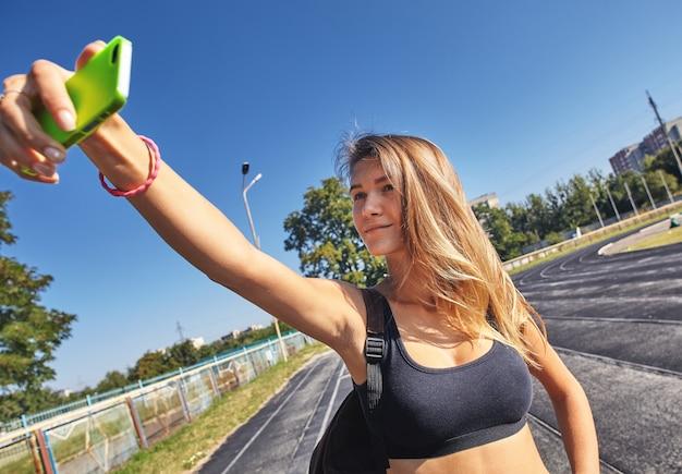 Garota feliz e saudável malhando e treinando enquanto tira selfies
