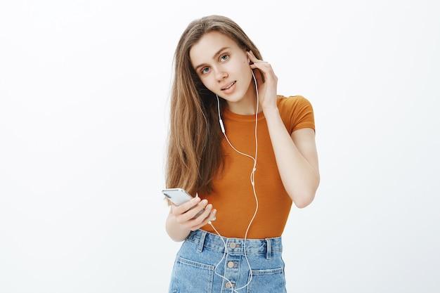 Garota feliz e sorridente coloca fones de ouvido, ouve podcast ou música no celular
