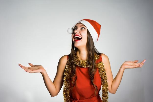 Garota feliz e sorridente com um boné vermelho, como se o papai noel estivesse comemorando o ano novo e o natal
