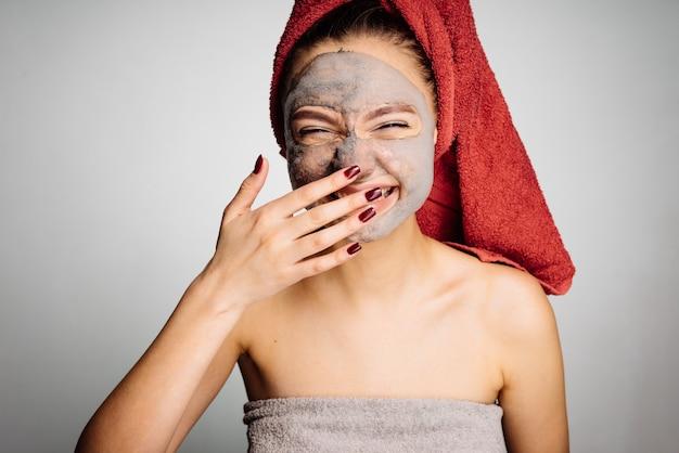 Garota feliz e sorridente com uma toalha vermelha na cabeça aplicou uma máscara útil no rosto