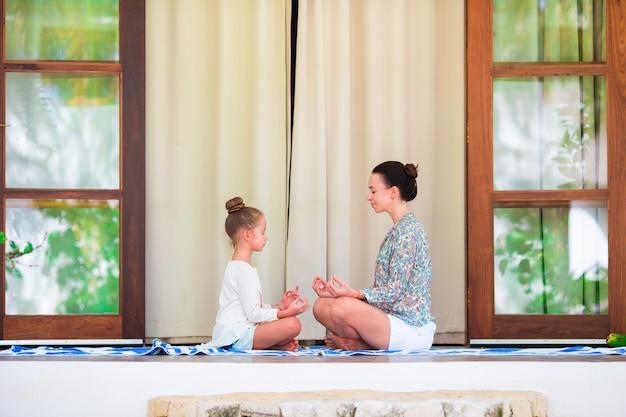 Garota feliz e sua mãe fazendo exercícios de ioga ao ar livre