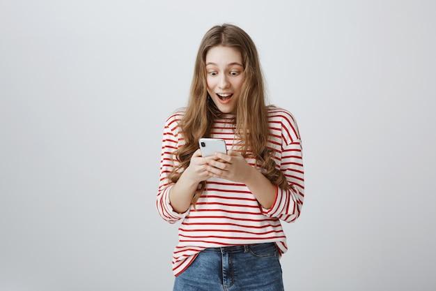 Garota feliz e surpresa lendo notícias incríveis na tela do smartphone Foto gratuita
