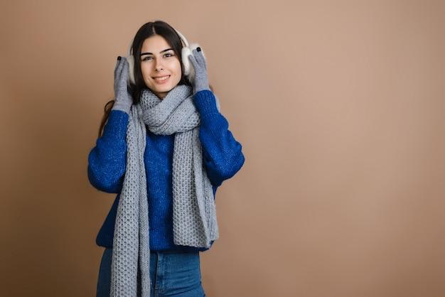 Garota feliz em fones de ouvido de pele, acessório quente e elegante