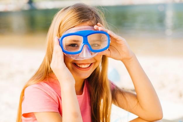 Garota feliz em máscara de mergulho na beira-mar