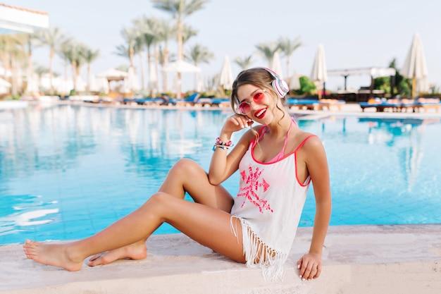 Garota feliz em óculos de sol da moda descansando à beira da piscina e ouvindo música favorita em grandes fones de ouvido