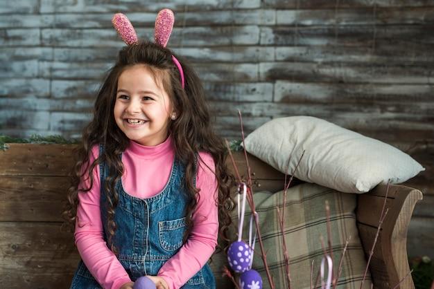Garota feliz em orelhas de coelho com ovos de páscoa
