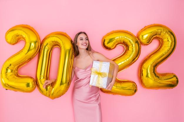 Garota feliz em pé perto de balões de ar enquanto segura uma caixa de presente na celebração do ano novo com fundo rosa