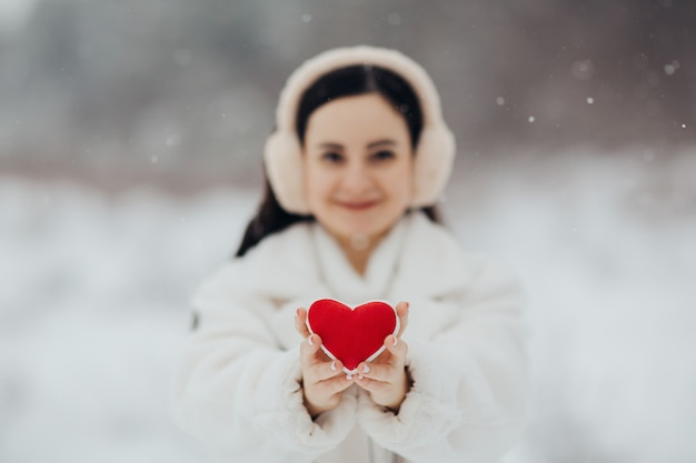 Garota feliz em roupas brancas quentes, segurando um coração vermelho em fundo nevado. dia dos namorados.