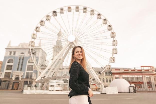 Garota feliz em roupas elegantes, de pé sobre o fundo de uma paisagem de rua e posando para a câmera