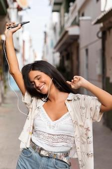 Garota feliz em tiro médio com fones de ouvido