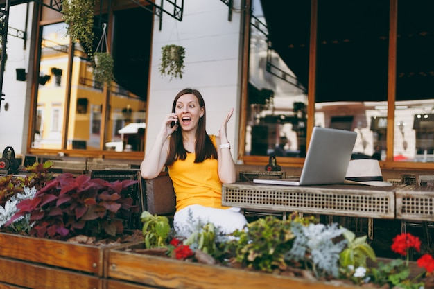 Garota feliz em um café ao ar livre na rua, sentada à mesa com o computador laptop pc, falando no celular, mantendo uma conversa agradável, no restaurante durante o tempo livre