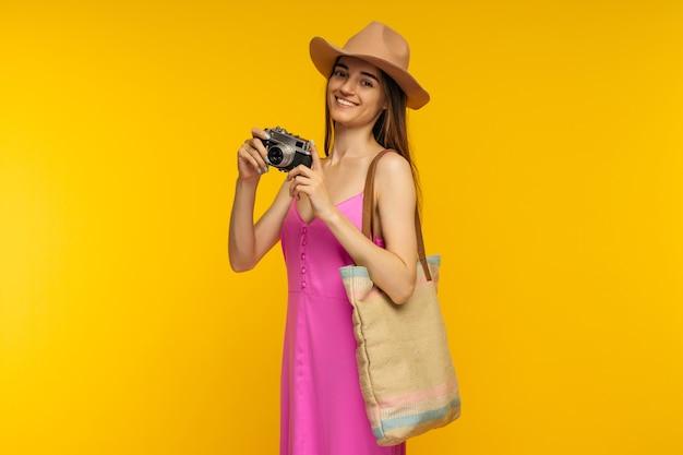 Garota feliz em um vestido rosa e óculos escuros segurando a câmera em uma imagem de fundo amarelo
