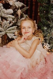 Garota feliz em um vestido rosa perto da árvore de natal
