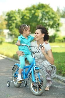 Garota feliz em uma bicicleta com a mãe no verão