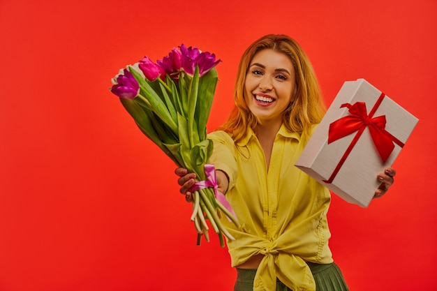 Garota feliz em uma blusa amarela mostra e abraça um buquê de tulipas e uma caixa de presente amarrada com uma fita vermelha para a câmera