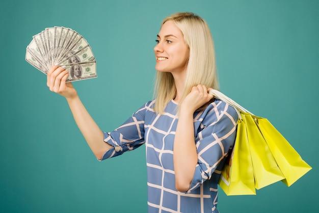 Garota feliz em uma blusa xadrez segurando notas de cem dólares e sacolas de compras
