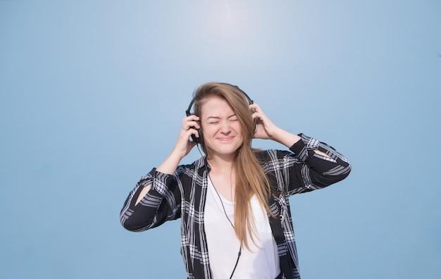 Garota feliz emocional com fones de ouvido na cabeça fica em um fundo azul, brilhante e ouve música
