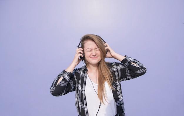 Garota feliz emocional com fones de ouvido na cabeça fica em um fundo roxo, brilhante e ouve música. estudante em roupas casuais ouve música no fundo de uma parede roxa.