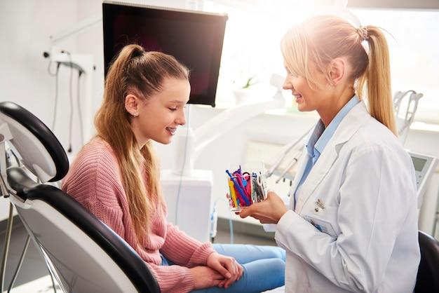 Garota feliz escolhendo a cor dos elásticos para o aparelho