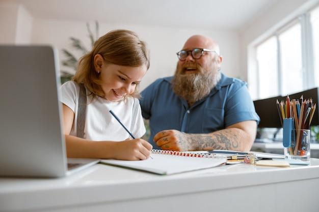 Garota feliz escrevendo em um caderno com o pai à mesa durante a vídeo-aula em casa