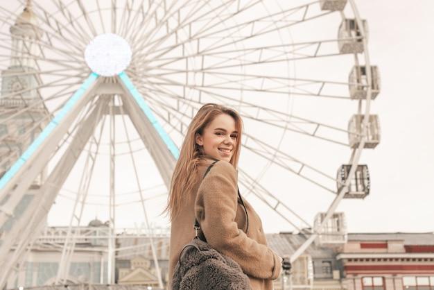 Garota feliz está de pé na rua no fundo de uma paisagem da cidade, vestindo roupas quentes e uma mochila, olhando a câmera e sorrindo