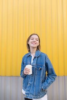 Garota feliz está de pé sobre fundo amarelo e bebendo café.