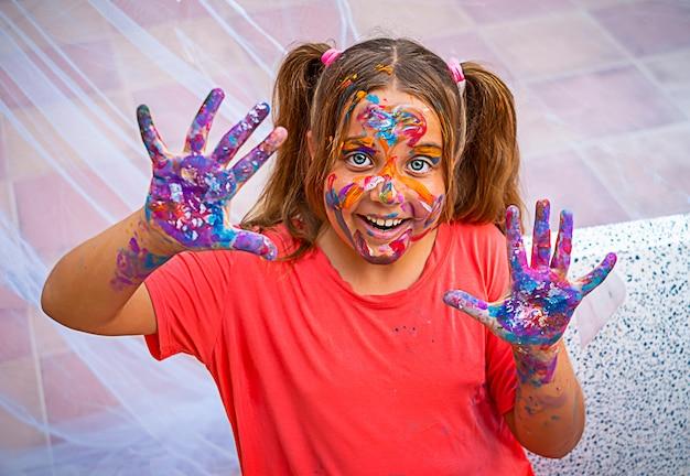 Garota feliz estava manchada de tinta. uma criança sorri com cores brilhantes no rosto, mãos e cabelos
