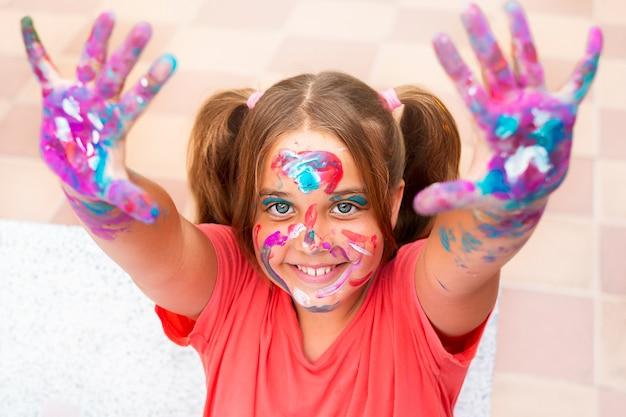 Garota feliz estava manchada de tinta. uma criança sorri com cores vivas no rosto, mãos e cabelo