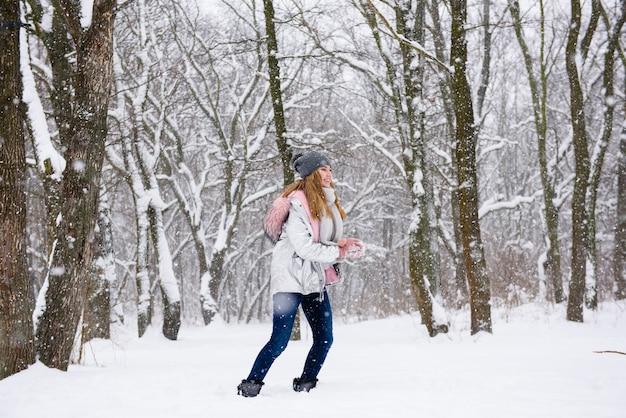 Garota feliz fazendo bola de neve ao ar livre
