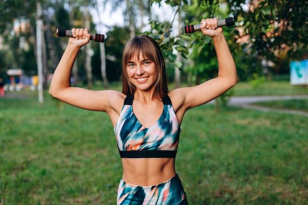 Garota feliz fazendo exercício esercise com halteres ao ar livre