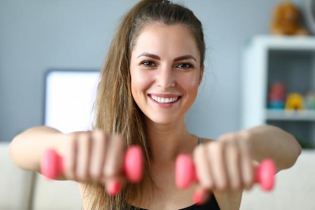 Garota feliz fazendo exercícios com halteres em casa