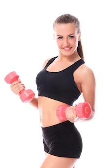 Garota feliz fazendo exercícios com halteres