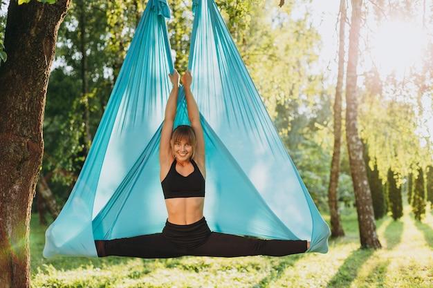 Garota feliz fazendo ioga voar ao ar livre, espalhando suas pernas bem separadas, olhando para a câmera