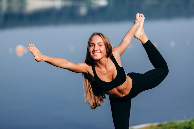 Garota feliz fazendo yoga asana e segura pela mão a perna nas costas.